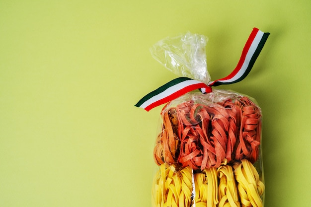 Colorful raw italian pasta in transparent plastic bag on green background. homemade colored pasta. Premium Photo