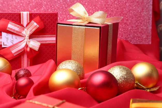 Colorful red gifts with christmas balls isolated on red Premium Photo