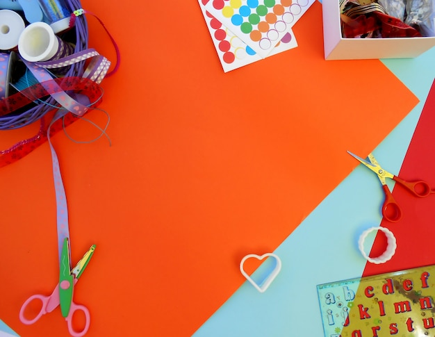 Colorful ribbons, box with threads, molds, scissors and ruler with letters on colorful bac Premium Photo