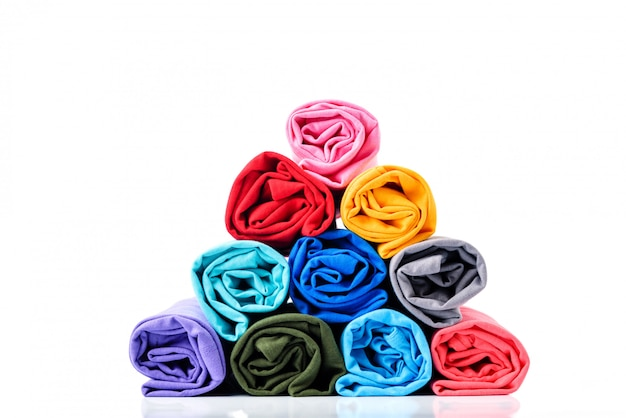 Colorful of rolls cotton t-shirt made to pyramid shape isolated on white background. Premium Photo
