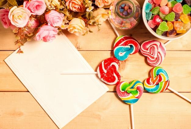 Разноцветные розы, цветы и пустой тег для вашего текста со сладким желе, вкусом фруктов, конфетами в форме сердца пастельных тонов на деревянном фоне Premium Фотографии