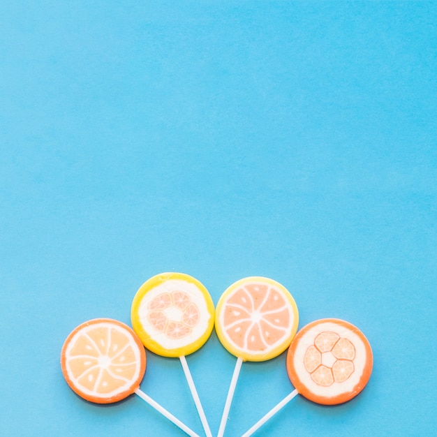 Colorful round lollipop candies arranged down over the blue background Free Photo