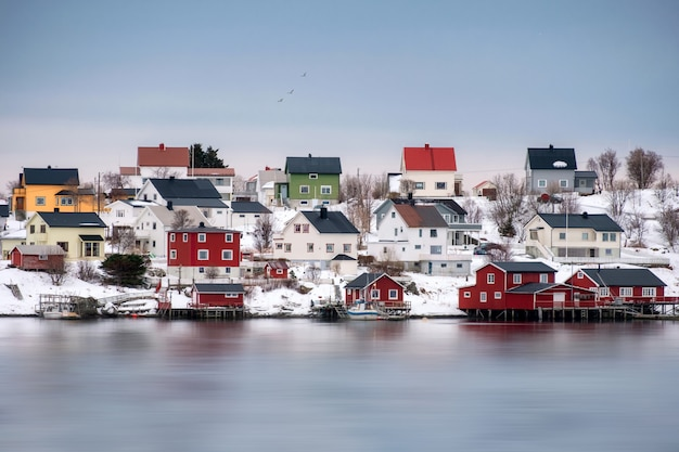 Colorful scandinavian wooden house on snowy at coastline Premium Photo