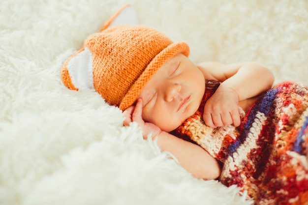 Colorful scarf covers little baby sleeping on the fluffy pillow Free Photo