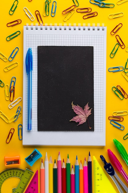 Colorful school stationery and chalkboard on yellow paper background Premium Photo