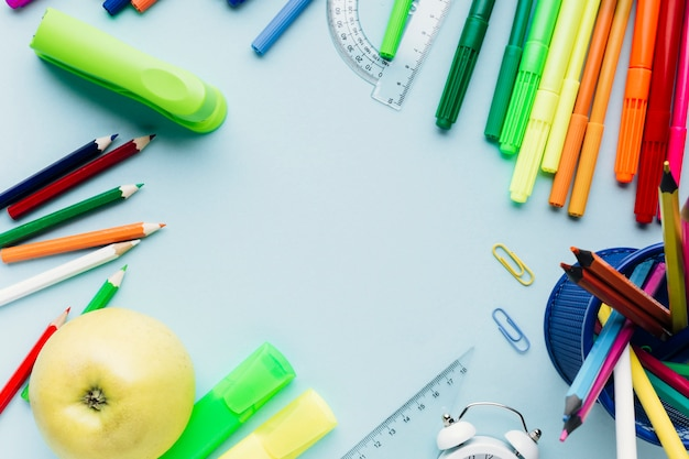 Colorful school stationery scattered around empty space on blue desk Free Photo
