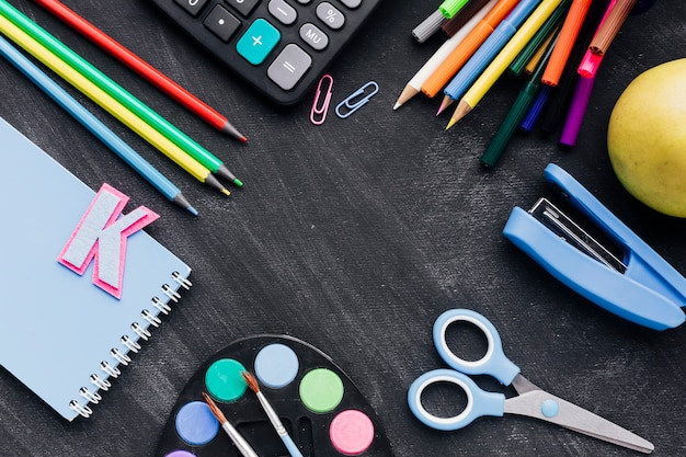 Colorful school stationery scattered on chalkboard Free Photo