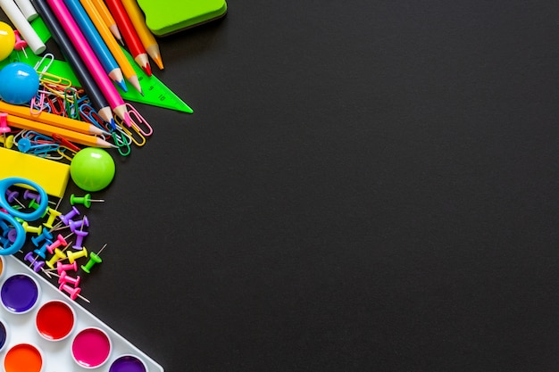 Colorful school supplies on black chalkboard background. Premium Photo