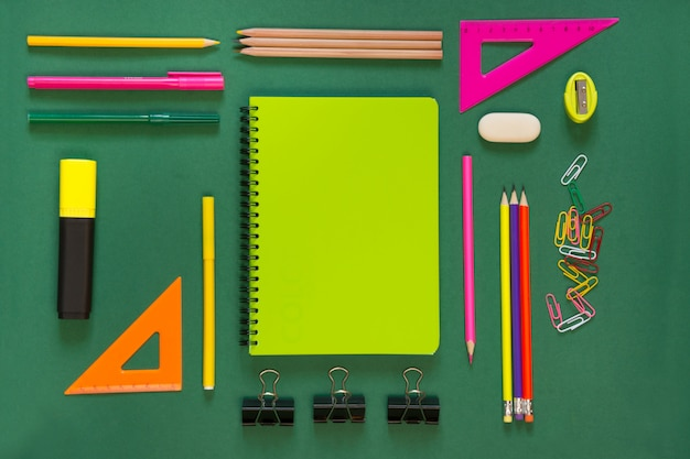 Colorful school supplies, green book on green. Premium Photo