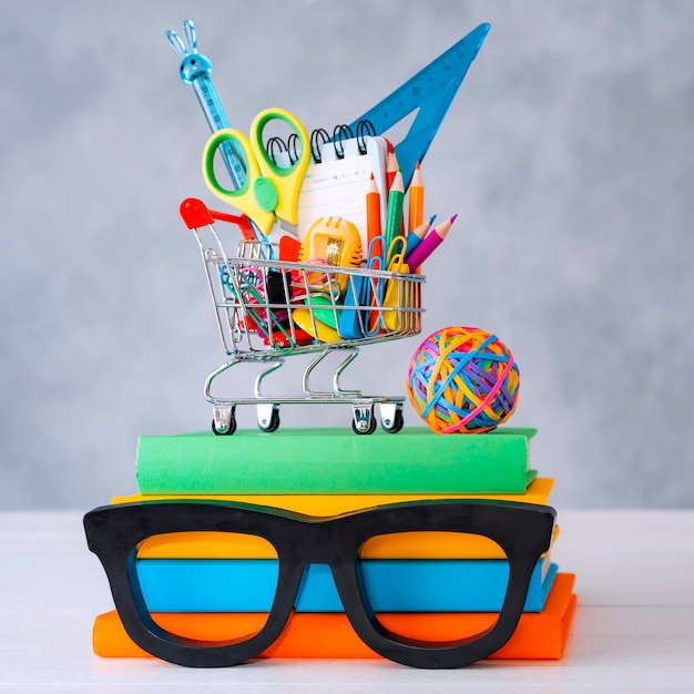 Colorful school supplies shopping basket gray wall with a copy text space. a stack of books with colorful covers frame glasses. the concept of returning to school for new academic year. Free Photo