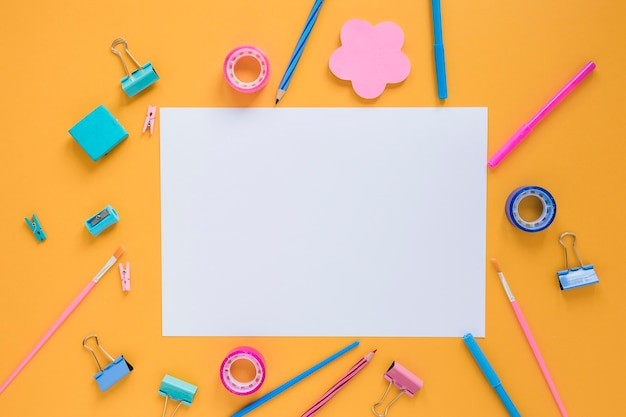 Colorful school supplies with blank paper in center Free Photo