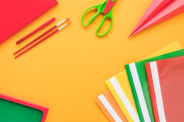 Colorful school supplies on yellow background Free Photo