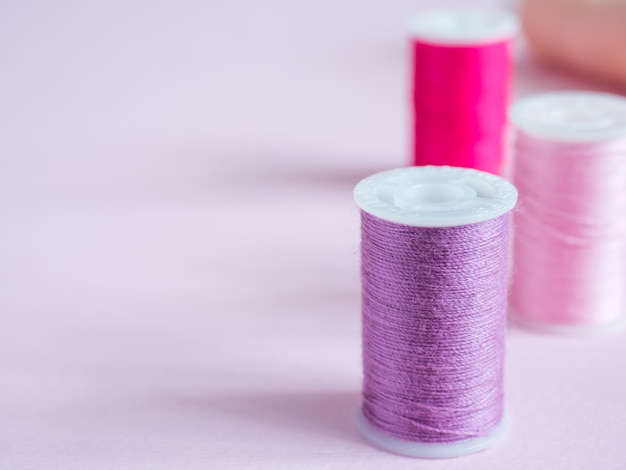 Colorful sewing buttons and thread on a pink background Premium Photo