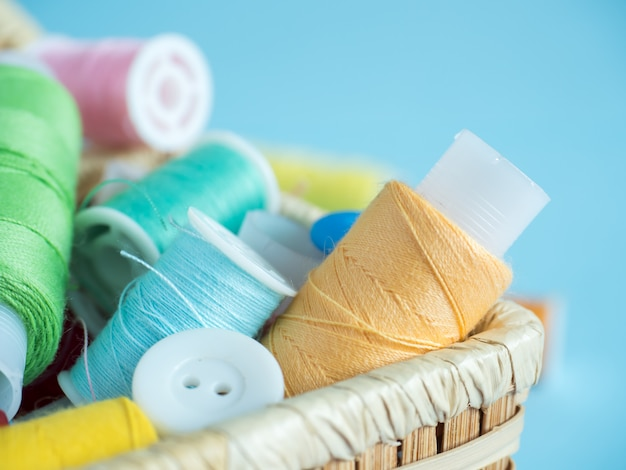 Colorful sewing buttons and thread in a wooden box on a blue background Premium Photo
