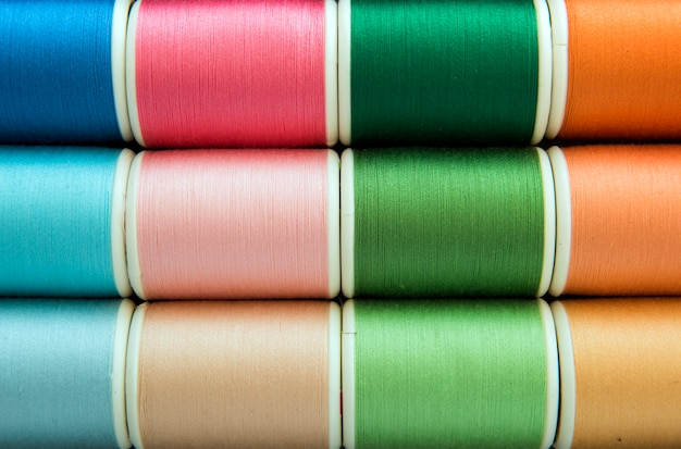 Colorful sewing threads background closeup Free Photo