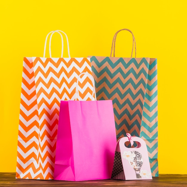 Colorful shopping bags with design on wooden table against yellow background Free Photo