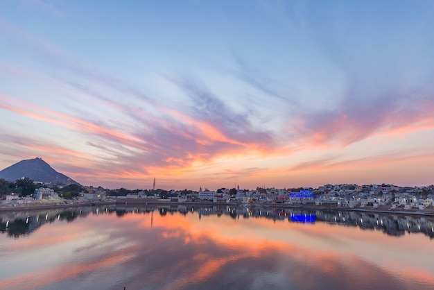 Colorful sky and clouds over pushkar, rajasthan, india. temples, buildings and colors reflecting on the holy water of the lake at sunset. Premium Photo