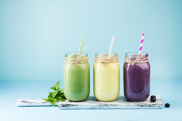 Colorful smoothie jars on blue background Free Photo