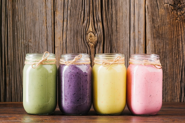 Colorful smoothie jars on wooden background Free Photo
