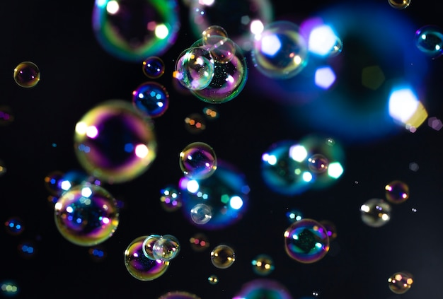 Colorful soap bubbles float in the dark Premium Photo