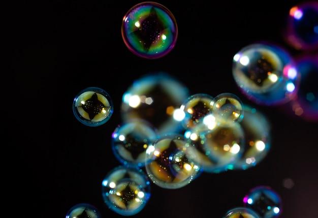 Colorful soap bubbles float in the dark. Premium Photo