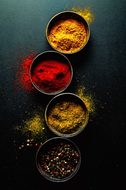 Colorful spices on dark table Free Photo