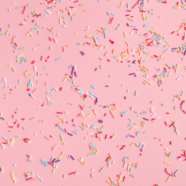 Colorful sprinkles scattered on table Free Photo