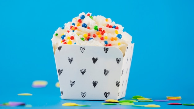 Colorful sprinkles on whipped cream in the box against blue backdrop Free Photo