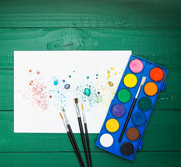 Colorful stains abstract painting on white paper with paintbrush and watercolor palette Free Photo
