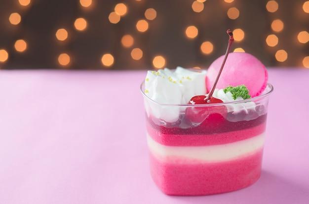 Colorful strawberry cake and macaron over shiny bokeh background Free Photo