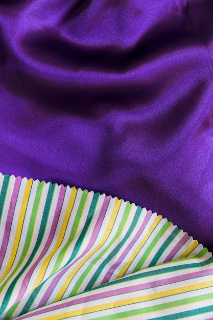 Colorful stripes pattern table cloth on smooth purple textile Free Photo