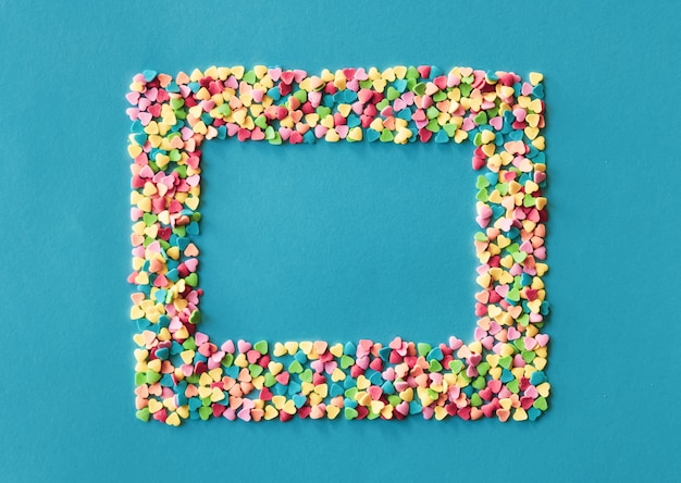 Colorful sugar heart shaped sprinkles frame on green blue background. valentines day concept. Premium Photo
