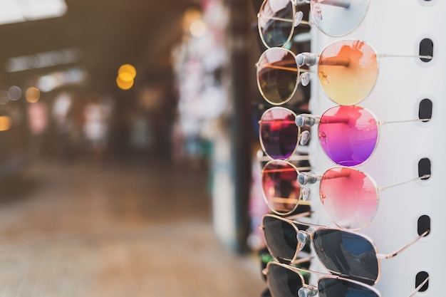 Colorful sunglasses hung in a row in front of the store in the market Premium Photo