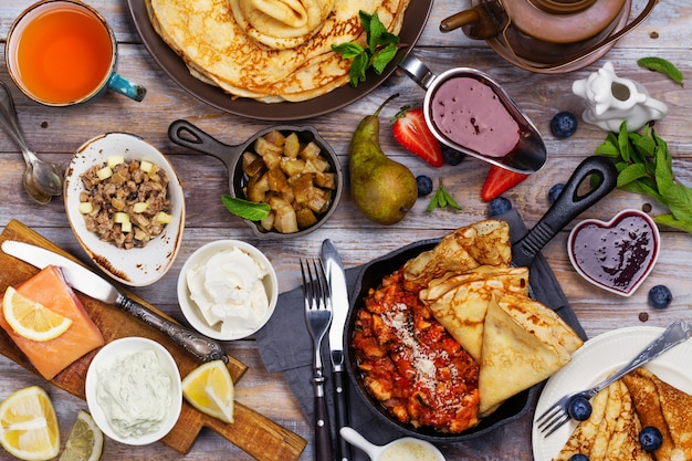 Colorful, tasty and savory breakfast with crepes and different fillings and sauces Premium Photo