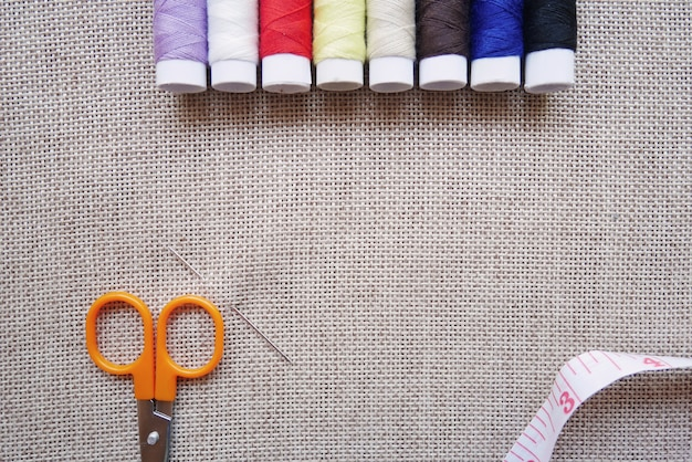 Colorful thread, scissors, measuring tape and pins on linen fabric Premium Photo