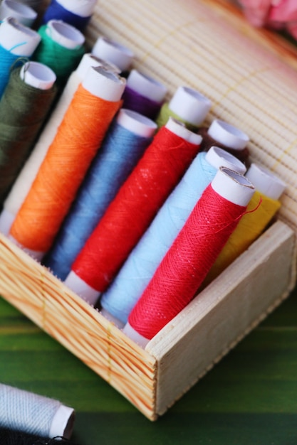 Colorful thread for sewing on wood background Premium Photo