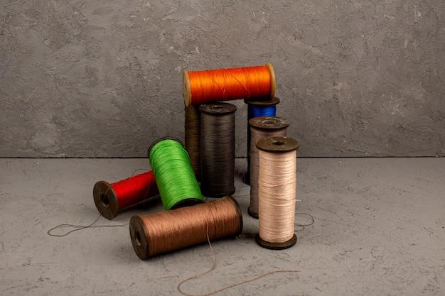 Разноцветные нитки для шитья на сером фоне Бесплатные Фотографии