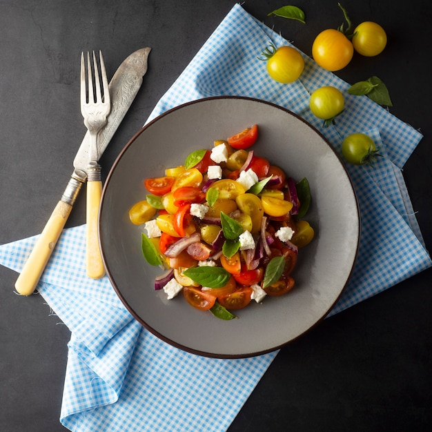 Colorful tomatoes and basil salad on a plate. healthy, summer food. Premium Photo