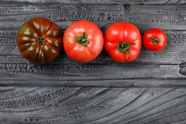 Красочный вид сверху помидоры на серой деревянной стене Бесплатные Фотографии