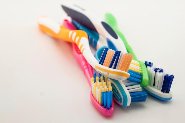 Красочные зубные щетки на белом фоне с копией пространства. макрос с мелкой степенями свободы. Premium Фотографии