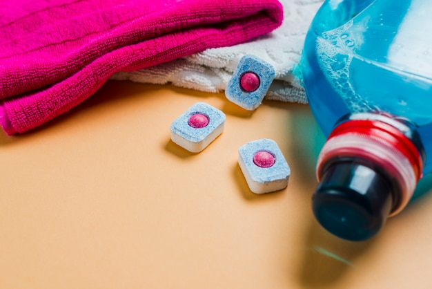 Colorful towels and liquid detergent with dishwasher tablets Free Photo