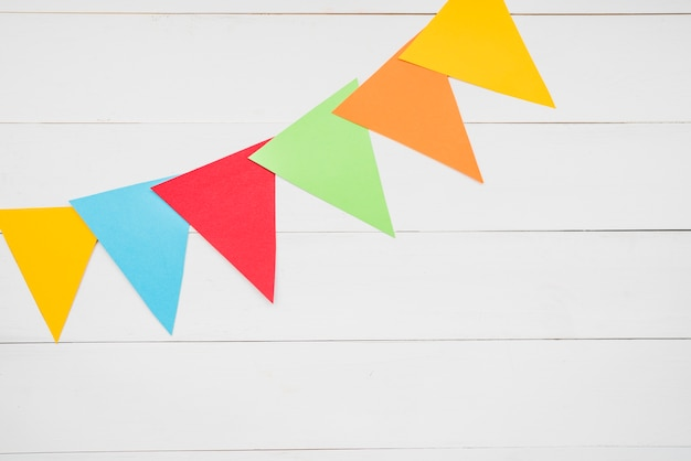 Colorful triangular bunting on white wooden plank Free Photo