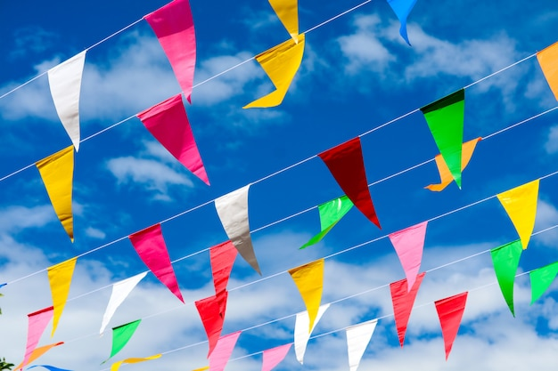Colorful triangular flag line moving by wind on blue sky white cloud Premium Photo