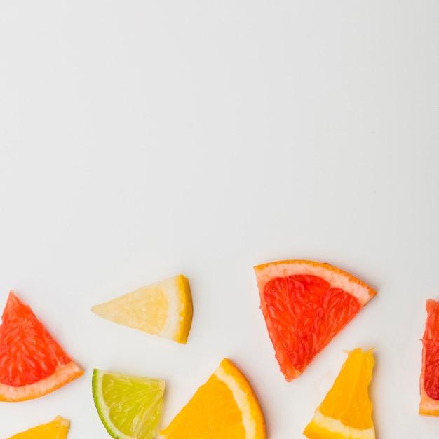 Colorful triangular slice of grapefruits; lemon and an orange on white background Free Photo