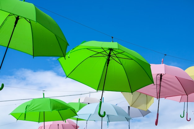 Colorful umbrella line decorate outdoor moving by wind on blue sky white cloud Premium Photo