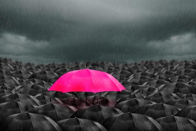 Colorful umbrella in mass of black umbrellas. Premium Photo