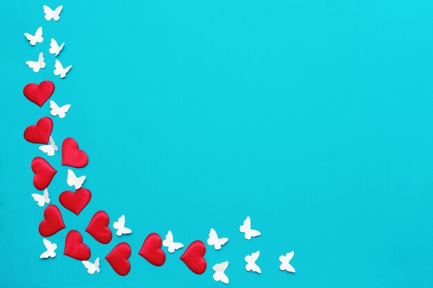 Colorful valentine background, greeting card made of red textile hearts and hand made white butterflies. love and valentine's day concept Premium Photo