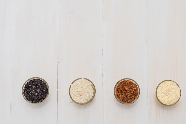 A colorful variety of rice in bowls arranged as a border over a wooden background Free Photo