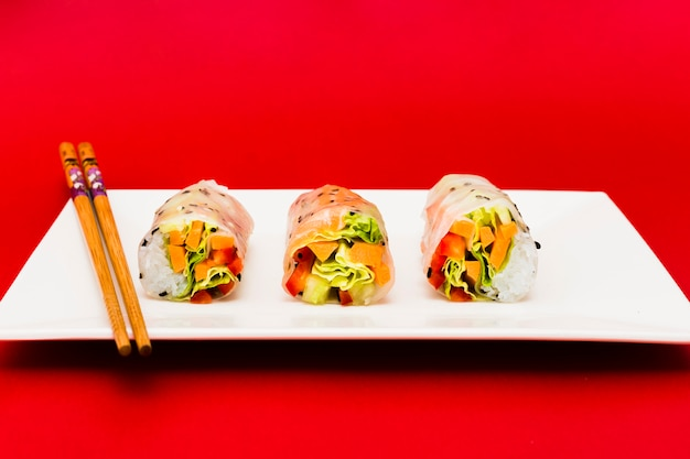 Colorful vegetables stuffed in rice spring rolls and chopsticks over white plate Free Photo