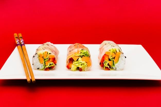 Verdure variopinte farcite in involtini primavera di riso e bacchette sul piatto bianco Foto Gratuite